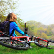 Stock Photo: Womcyclist relaxing, face to sun's rays. At halt