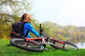 žena cyklista relaxační, tvář slunečním paprskům. na zastavení — Stock fotografie