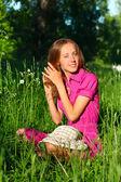 Vacker kvinna sitter i gräset och strök hennes hår — Stockfoto