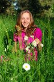 Mulher bonita sorrindo entre as gramíneas e margaridas — Foto Stock