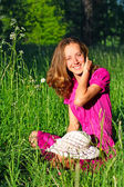 Beautiful woman sitting in grass and laughs — Stock Photo