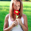 Stock Photo: Portrait of young woman with plushy flower in hand