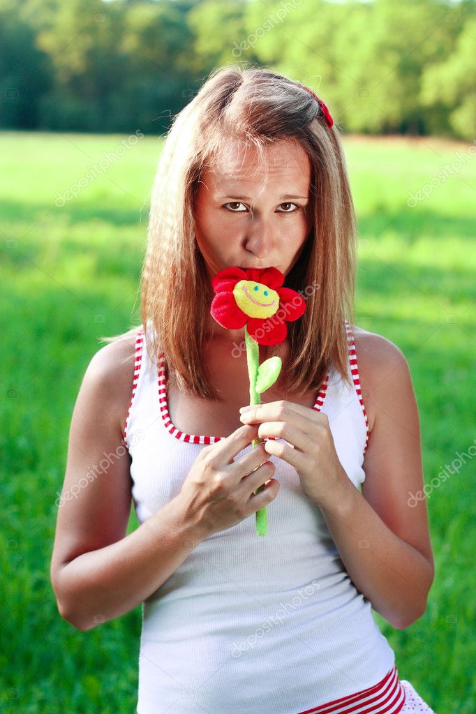Portrait of young woman with plushy flower in hand. Background blur — Stock Photo #6217399
