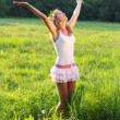 Woman is standing on meadow and her look and hands are raised up - Stock Photo