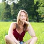 Beautiful young woman relaxing on green grass — Stock Photo