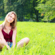 Beautiful young woman relaxing on green grass — Stock Photo