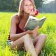 Young woman sitting in grass reading book an apple in his hand — Stock Photo