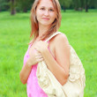 A smiling girl in a pink dress and a bag on his shoulder — Stock Photo #6324105