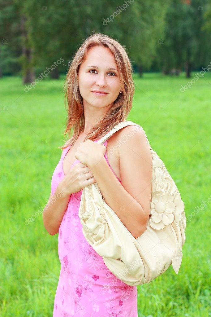 A smiling girl in a pink dress and a bag on his shoulder. Nature of the background — Stock Photo #6324105