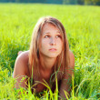 Portrait of young beautiful woman lying on green grass — Stock Photo