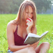 Woman sitting in grass reading book an nectarine in his hand — Stock Photo #6494668