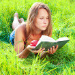 Stock Photo: Young woman lying in grass reading book an nectarine in his hand