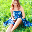 Young woman sitting in grass reading book — Stock Photo