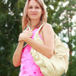 A smiling girl with a book in hand and a handbag on his shoulder — Stock Photo #6494805