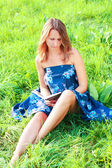 Jovem mulher sentada na grama lendo livro — Foto Stock