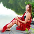 Foto Stock: Beautiful womwrapped red shawl on coast pond