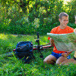 Young couple tourist with map in hand sitting on the grass — Stok fotoğraf