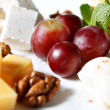 Cheese in the assortment of grapes and walnuts — Stock Photo
