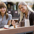 Two young smiling lady in cafe — Stok fotoğraf