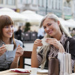Smiling girl drinking a coffee - Stockfoto