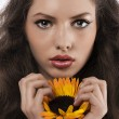 Natural girl with long hair holding a sunflower — Stock Photo