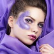 Young girl laying on purple fabric wearing glitter make up - Foto Stock