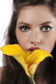 Zoom on a girls face with a yellow calla — Stock Photo