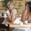 Girl friends in a cafe - Stock Photo