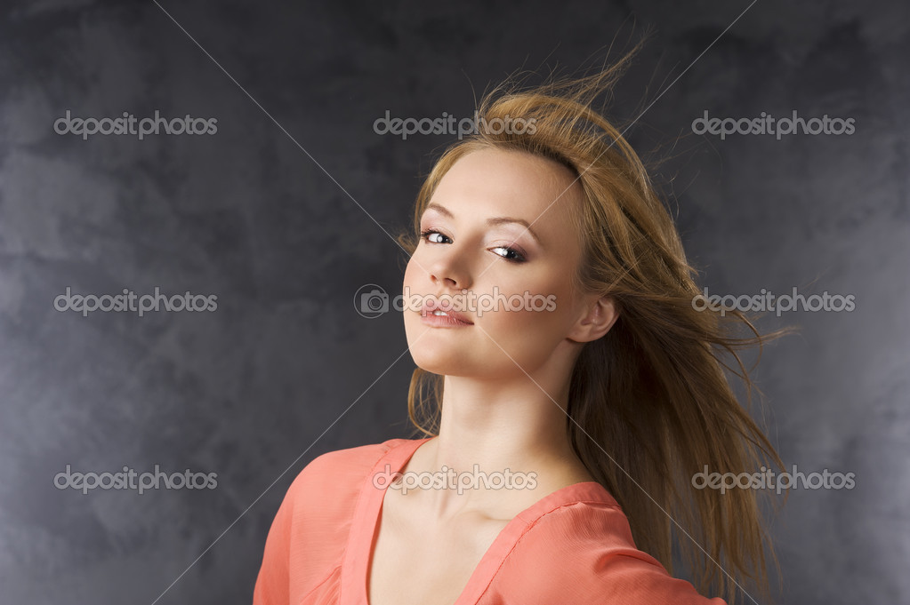 Beauty portrait of a blond woman with orange dress and wind in her hair — Stock Photo #6264604