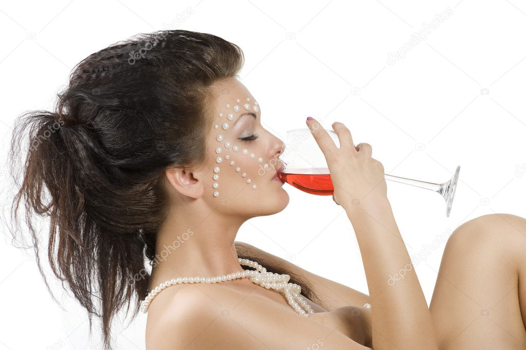 Naked sexy woman with hair style and pearl on face drinking from a glass red ...