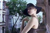 Young blond fashion woman in elegant black hat in urban backgro — Stock Photo