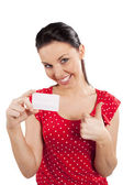 Woman in red with card smiling — Stock Photo