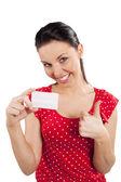 Mujer vestida de rojo con tarjeta sonriendo — Foto de Stock