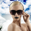 Fashion shot of blond girl with sunglasses looking at the camera — Stockfoto