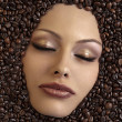Stock Photo: Girl's face immersed in coffee beans