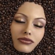 Girl's face immersed in coffee beans - Zdjęcie stockowe