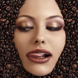 Close up portrait of a girl&#039;s face immersed in coffee beans - Stock Photo