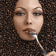 Face shot of a beautiful girl immersed in coffee beans - Stock Photo