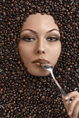 Tiro de cara de una chica hermosa inmersa en granos de café — Foto de Stock