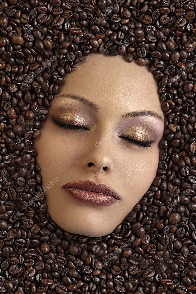Close up of a girl's face immersed in coffee beans keeping her eyes closed — Stock Photo #6632853