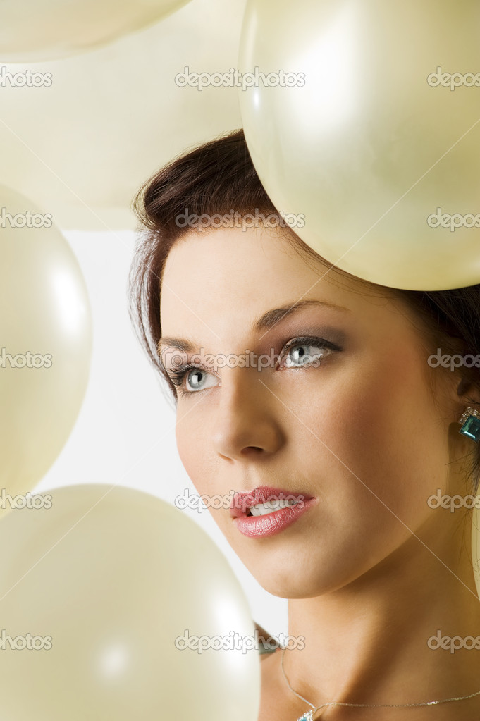 Close up portrait of a young pretty brunette with air balloons around her face  Stock Photo #6688474