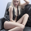 Sexy blonde sitting on a sofa — Stock Photo #6702936