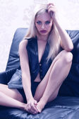Beautiful blonde posing on a black sofa — Stock Photo