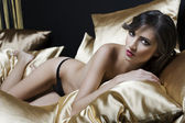 Sexy naked girl between pillow — Stock Photo