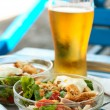Salad of meet, crackers and vegetables and glass of beer - Stock Photo