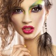 Young attracive female face with multicolored make-up - Stock Photo