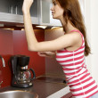 Woman standing at the kitchen — Stock Photo #5735892