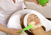 年轻女子与她脸上越来越掩码治疗皮肤美容 — 图库照片