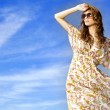 Beautiful girl in sunglasses on background blue sky - 