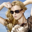 Stock Photo: Beautiful girl in sunglasses on background blue sky